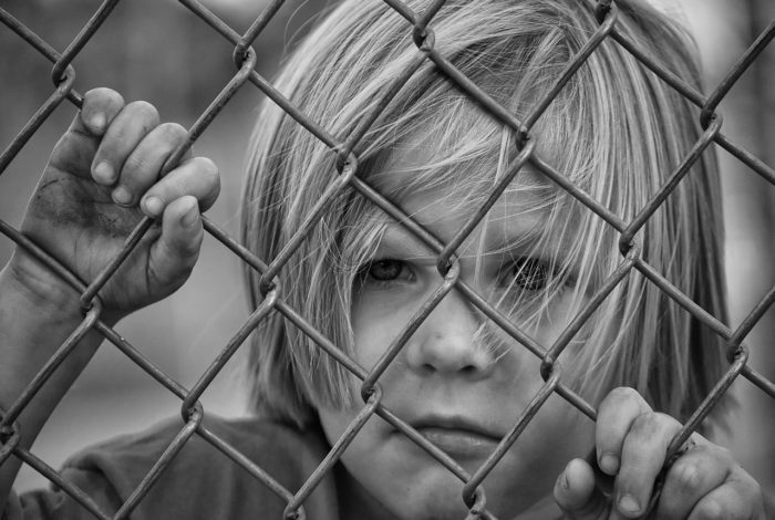BW photo of Little boy behind wire fence